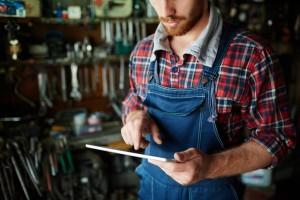 Modern repairman in uniform working on touchpad