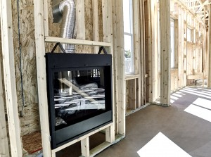 Framed home showing installation of a gas fireplace with vent