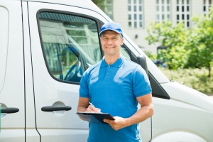 Young Happy Male Worker In Front Of Truck Writing On Clipboard