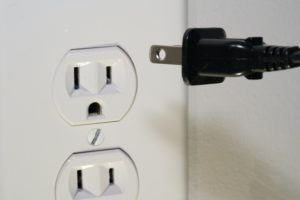 plug going into electrical outlet